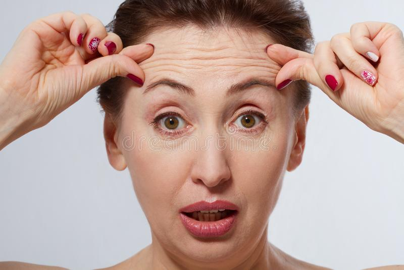 Cara macro da mulher com os enrugamentos na testa Conceito das injeções do colagênio e da cara menopause imagens de stock