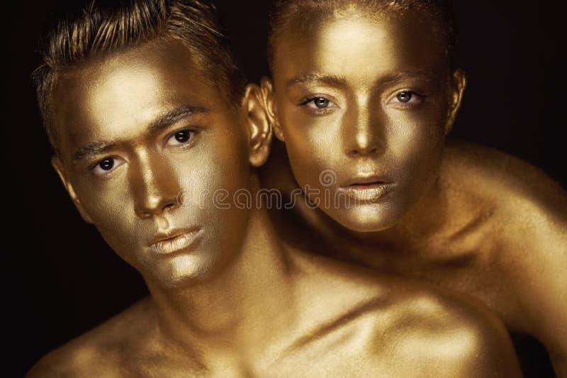 Cara masculina e fêmea ao redor A cabeça do ` s da mulher encontra-se no ombro de um homem Tudo pintado na pintura do ouro, o sen fotografia de stock royalty free