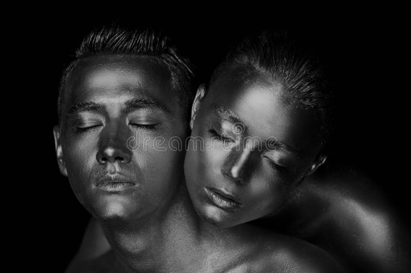 Cara masculina e fêmea ao redor A cabeça do ` s da mulher encontra-se no ombro de um homem Tudo pintado na pintura do ouro, o sen imagens de stock