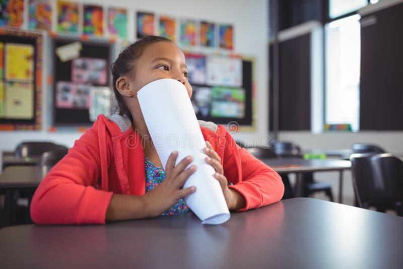 Cara pensativa de la cubierta de la muchacha con los papeles mientras que se sienta en el escritorio fotografía de archivo libre de regalías