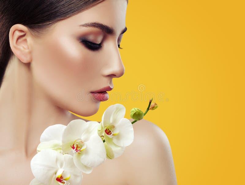 Cara perfeita nova da mulher com composição e flores da orquídea imagem de stock royalty free