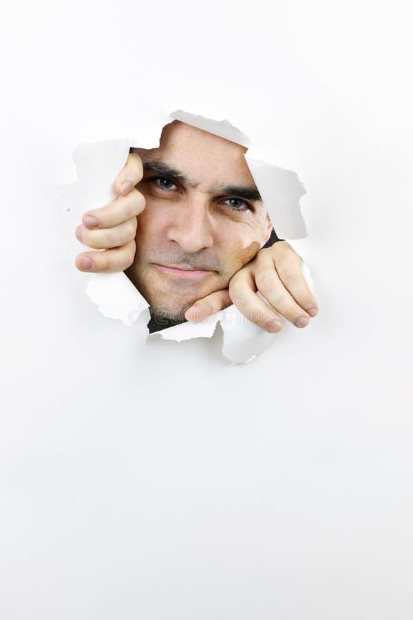 Cara que mira a través del agujero en papel fotos de archivo
