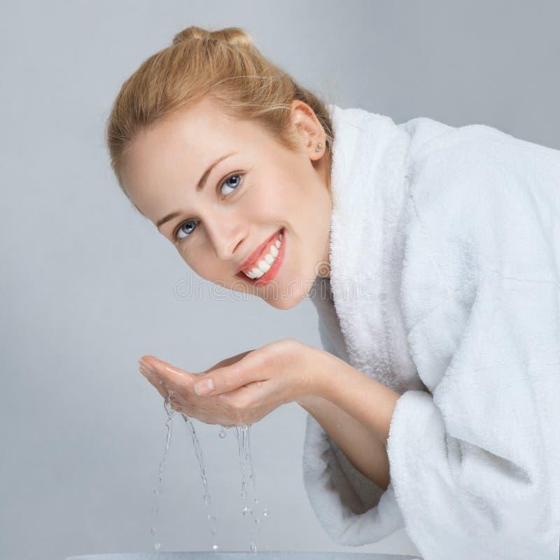 Cara que se lava de la mujer joven imagenes de archivo