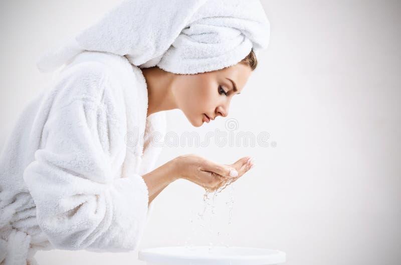 Cara que se lava de la mujer joven con el agua potable imágenes de archivo libres de regalías
