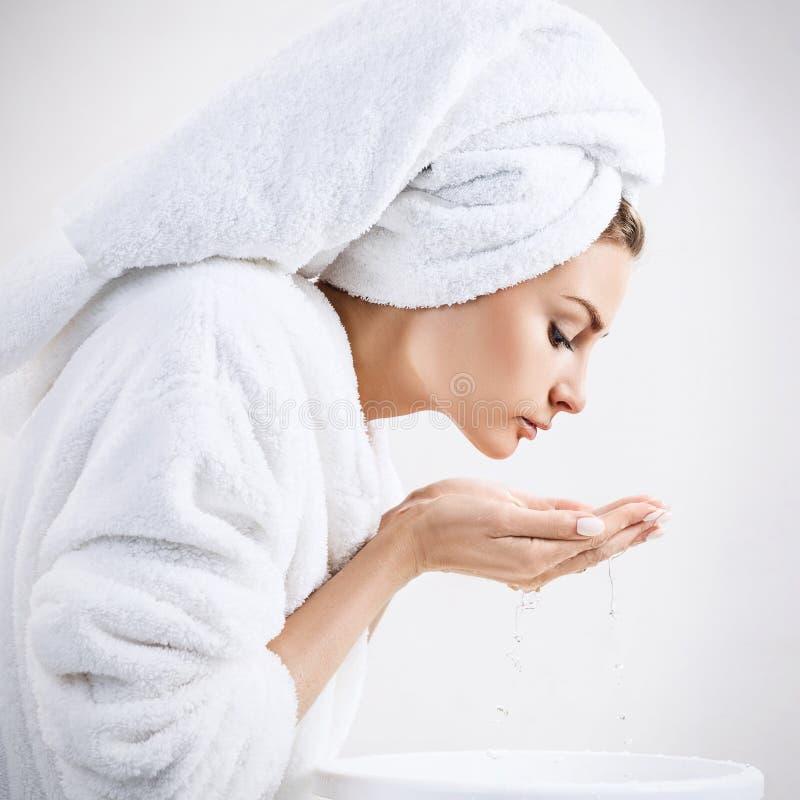 Cara que se lava de la mujer joven con el agua potable foto de archivo libre de regalías