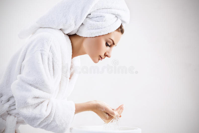 Cara que se lava de la mujer joven con el agua potable imagenes de archivo