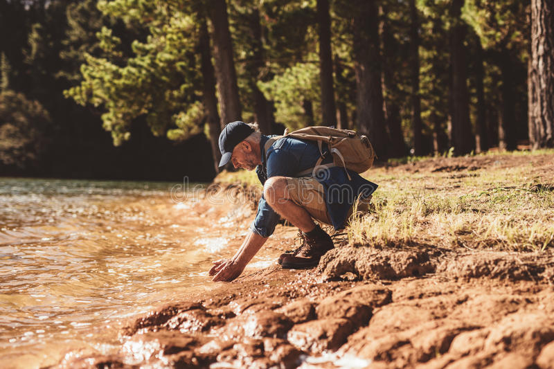 Cara que se lava del caminante masculino maduro en el lago foto de archivo