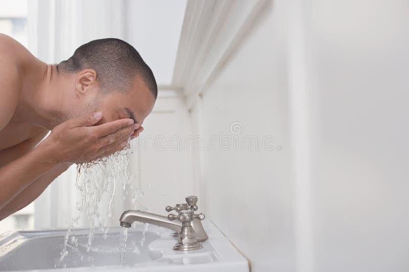 Cara que se lava del hombre en fregadero fotografía de archivo libre de regalías