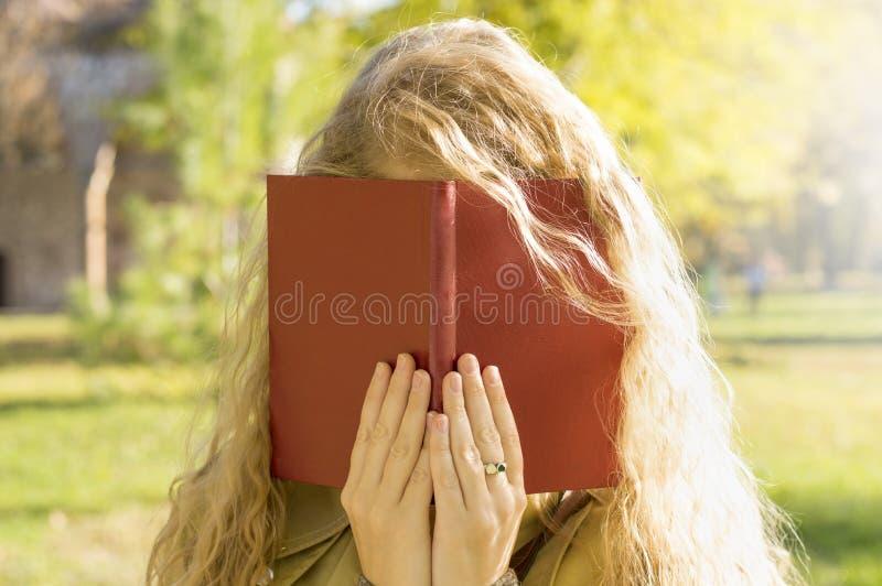 Cara rubia de la cubierta de la muchacha con un libro fotografía de archivo