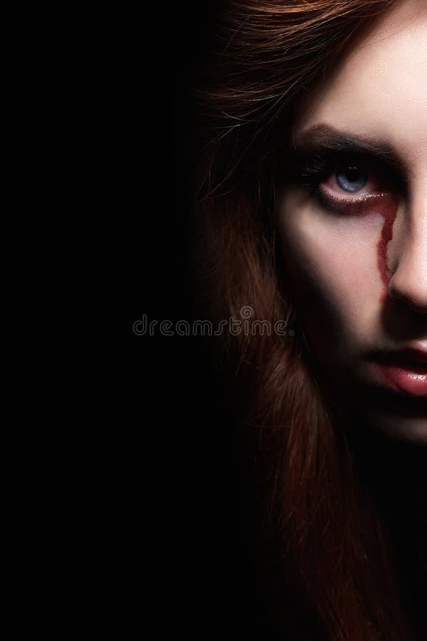 Cara sangrienta de la mujer en la oscuridad fotografía de archivo