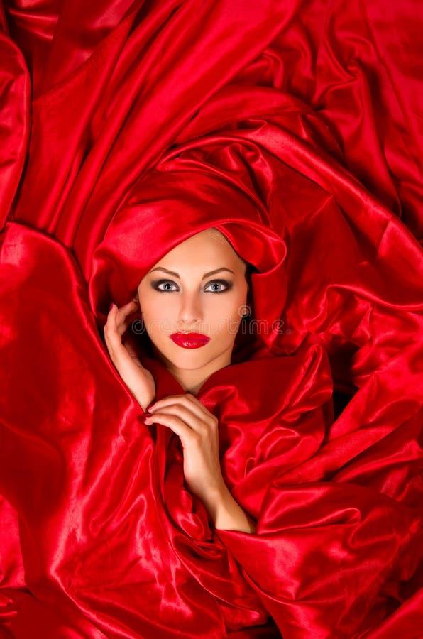 Cara sensual en tela de satén roja imagenes de archivo