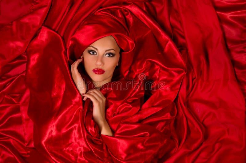 Cara sensual en tela de satén roja imagen de archivo