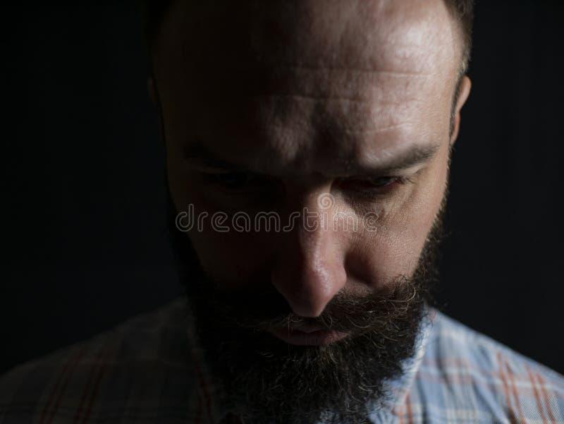 Cara seria de un hombre elegante con un primer de la barba y del bigote que mira a la parte inferior en un fondo negro imagenes de archivo
