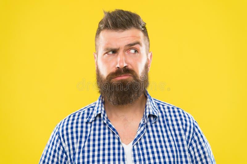 Cara seria del hombre que aumenta la ceja no confiada Tenga algunas dudas Cara barbuda del inconformista no segura en algo dudoso imagenes de archivo