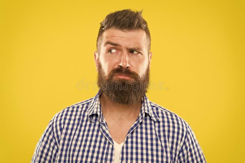 Cara seria del hombre que aumenta la ceja no confiada Tenga algunas dudas Cara barbuda del inconformista no segura en algo dudoso fotografía de archivo libre de regalías