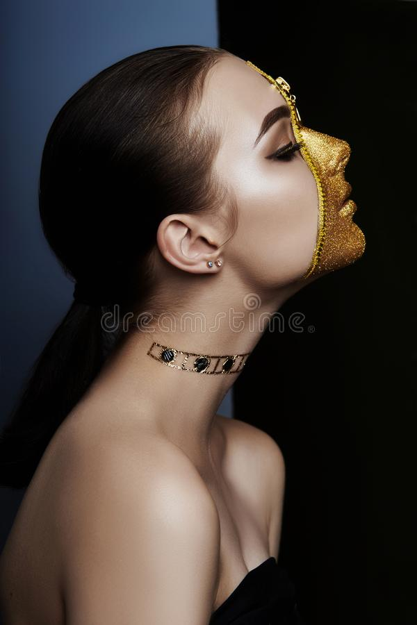 Cara severa creativa del maquillaje de la ropa de oro de la cremallera del color de la muchacha en piel Forme a belleza los cosmé imágenes de archivo libres de regalías