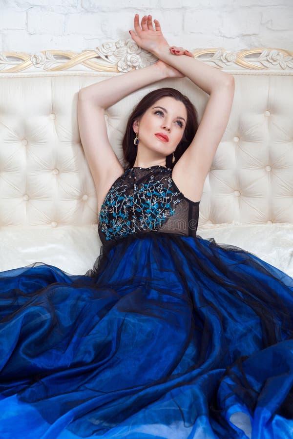 Cara sonhadora atrativa da mulher moreno com composição bonita no vestido de nivelamento azul que levanta ao sentar-se na cama e  imagens de stock royalty free