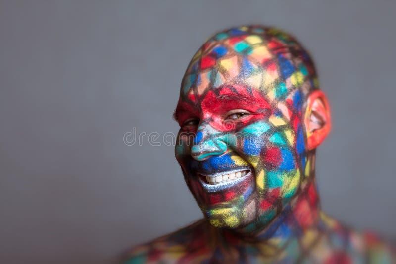 Cara sonriente colorida del malvado malévolo que le mira imagenes de archivo