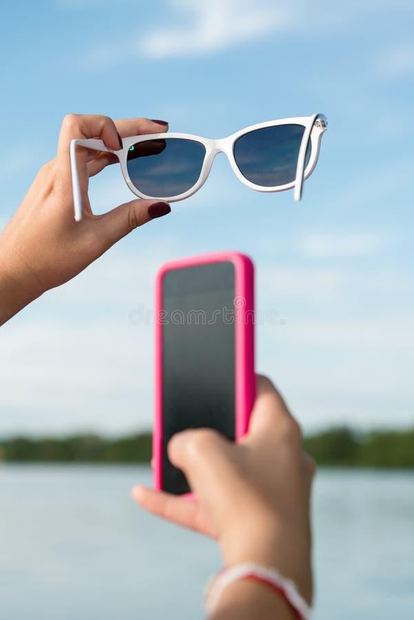 Cara sonriente con smartphone y las gafas de sol foto de archivo libre de regalías