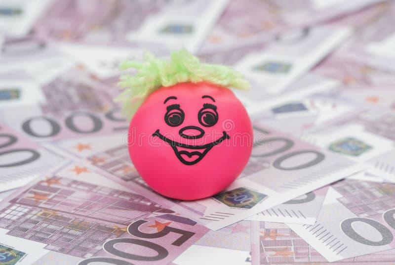 Cara sonriente de la bola en el dinero foto de archivo libre de regalías
