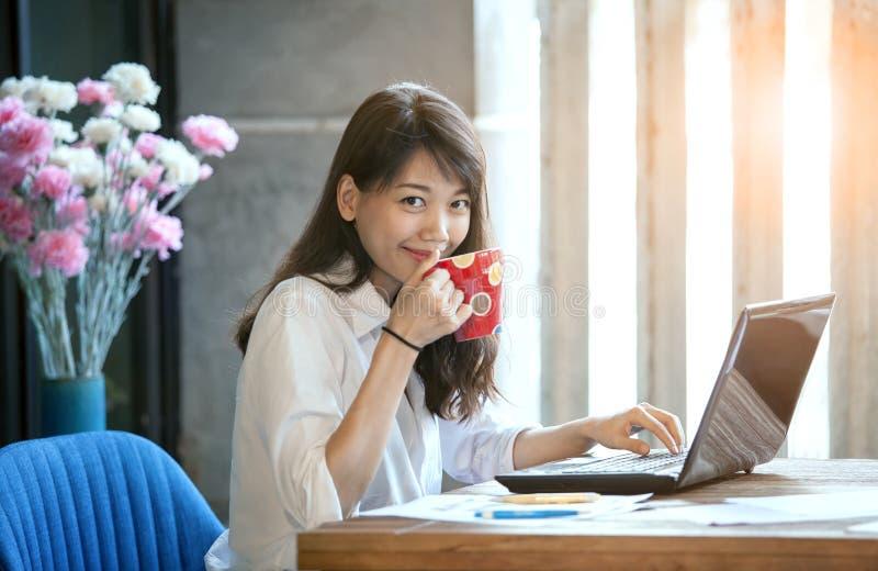 Cara sonriente de la felicidad de la mujer asiática joven que bebe el café caliente imagenes de archivo