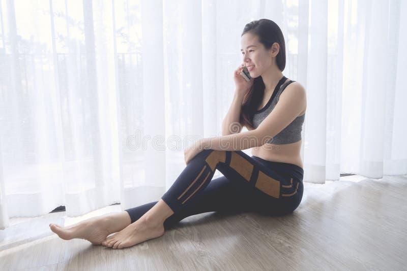 Cara sonriente de la mujer asiática joven en sujetador del deporte que habla en el teléfono imagen de archivo