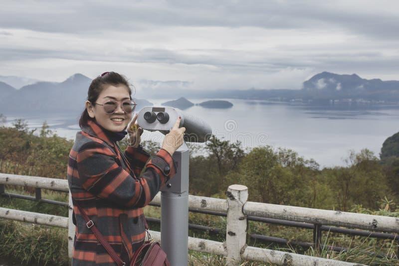 Cara sonriente dentuda de la felicidad de la mujer asiática que se coloca en surveillan foto de archivo libre de regalías