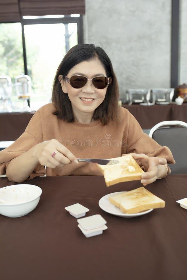 Cara sonriente dentuda de la mujer asiática con mantequilla y pan a disposición imagen de archivo libre de regalías