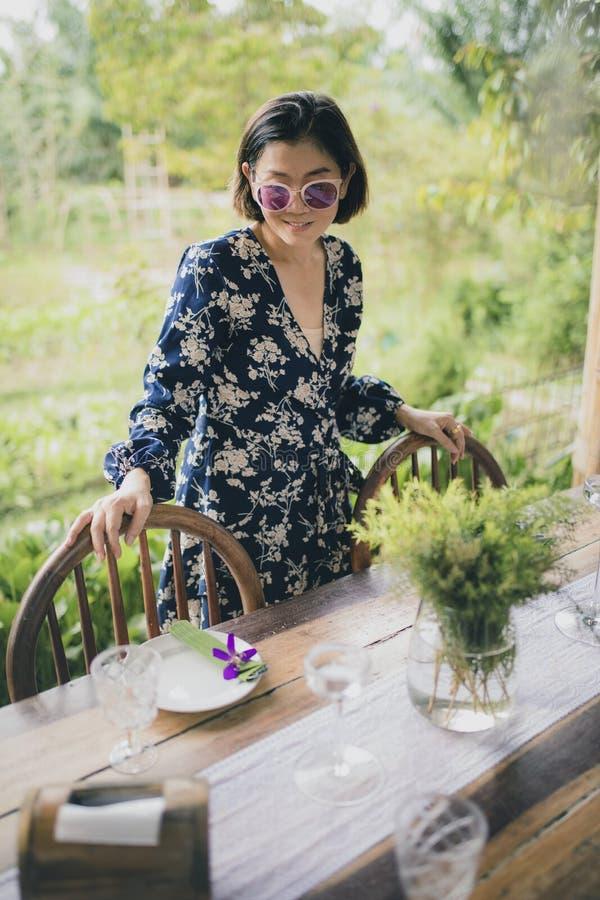 Cara sonriente dentuda de la mujer asiática hermosa con la emoción de relajación al lado de la tabla de la comida fotos de archivo