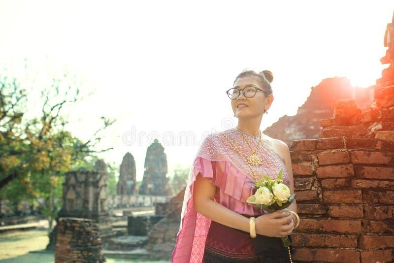 Cara sonriente dentuda de la mujer tailandesa que se coloca con la flor de loto rosada b imágenes de archivo libres de regalías