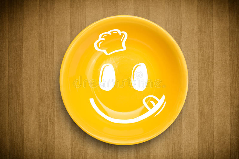 Cara sonriente feliz de la historieta en la placa colorida del plato fotos de archivo libres de regalías