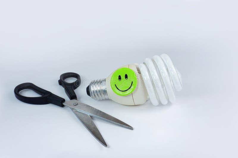 Cara sonriente feliz del bulbo ahorro de energía de las tijeras aislada en el fondo blanco foto de archivo