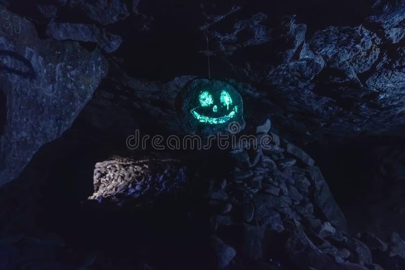 Cara sonriente fosforescente que brilla intensamente espeluznante oscura en piedra colgante en cueva imágenes de archivo libres de regalías
