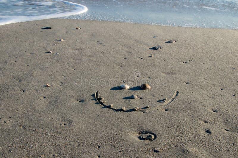 Cara sonriente hecha de cáscaras en la playa foto de archivo