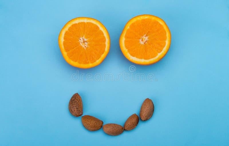 Cara sonriente sana con las naranjas y las almendras foto de archivo