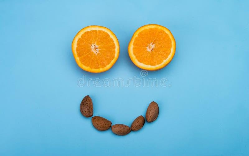Cara sonriente sana con las naranjas y las almendras fotos de archivo