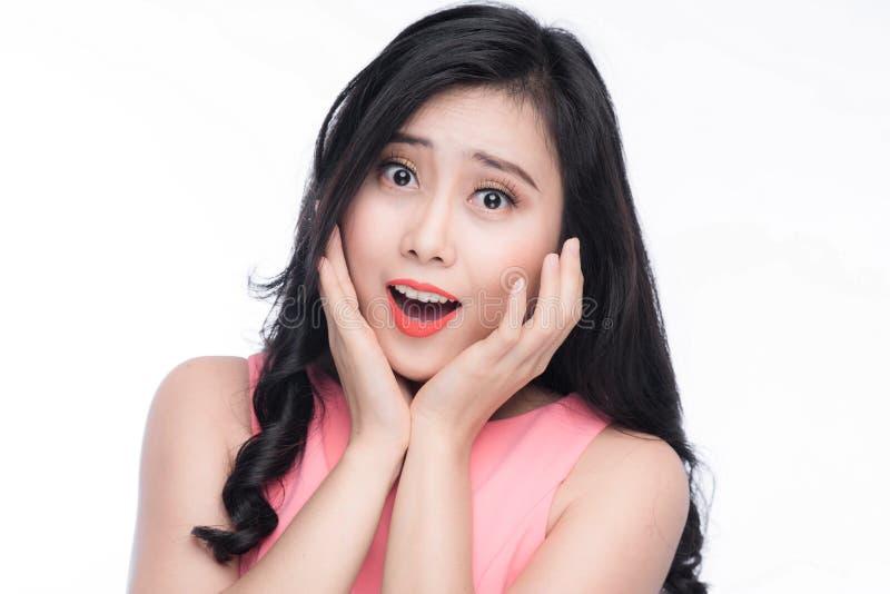 Cara sorprendida de la mujer asiática joven sobre blanco imagenes de archivo