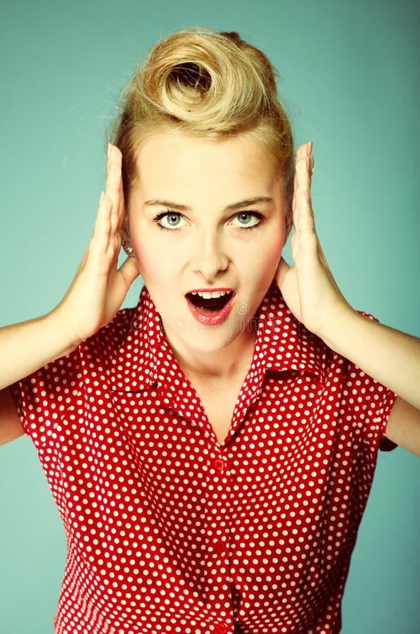 Cara sorprendida de la mujer joven sobre azul imagen de archivo libre de regalías