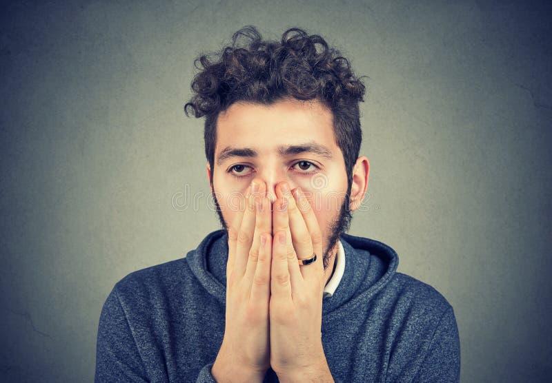 Cara triste de la cubierta del hombre en la desesperación foto de archivo