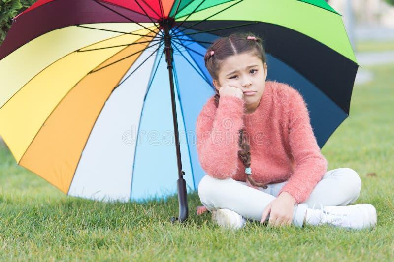 A cara triste só da criança da menina senta o parque sob o guarda-chuva Estada positiva e otimista Influência positiva acessória  imagem de stock