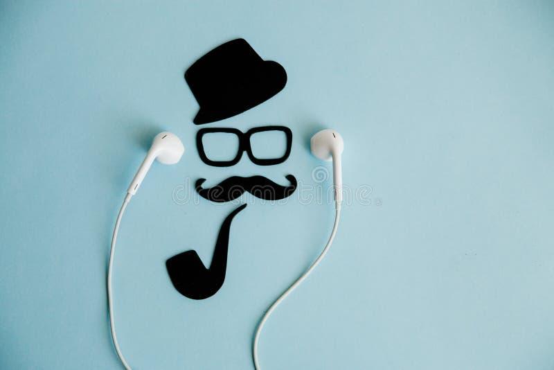 Cara y bigotes masculinos, y música que escucha de la imagen del caballero de los accesorios con los auriculares fotos de archivo libres de regalías