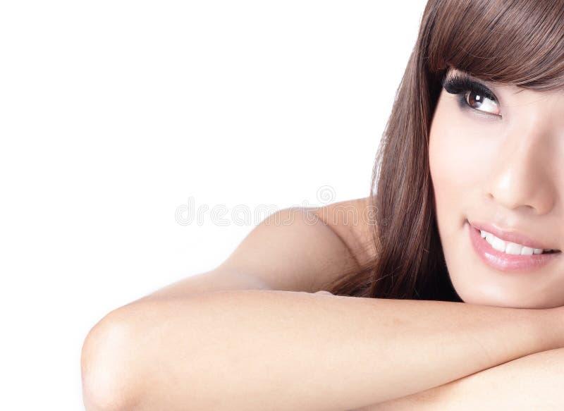 Cara y mirada de la sonrisa de la muchacha para esconder el espacio de la copia fotografía de archivo