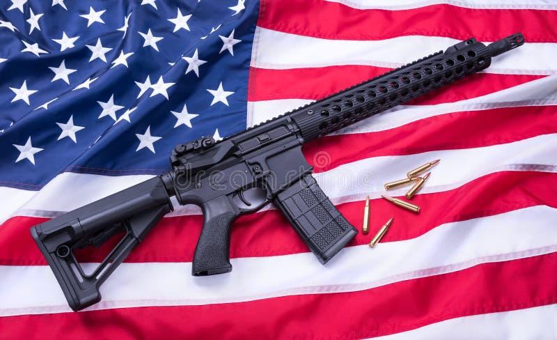 Carabina AR-15 y balas a la medida en la superficie de la bandera americana, fondo Tiro del estudio fotos de archivo