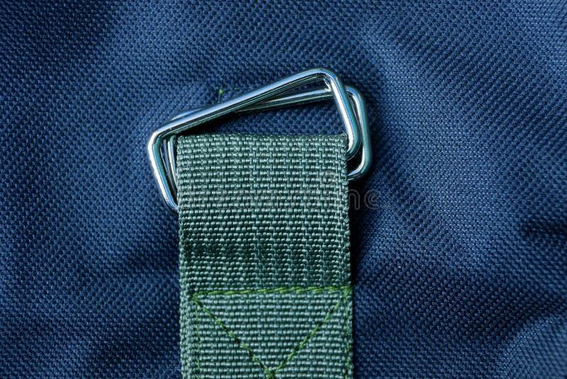 Carabina gris del metal en un arnés verde cosido a la tela negra imagenes de archivo