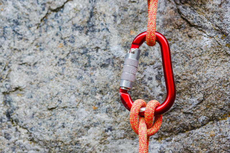 Carabiner with rope on rocky background royalty free stock photo