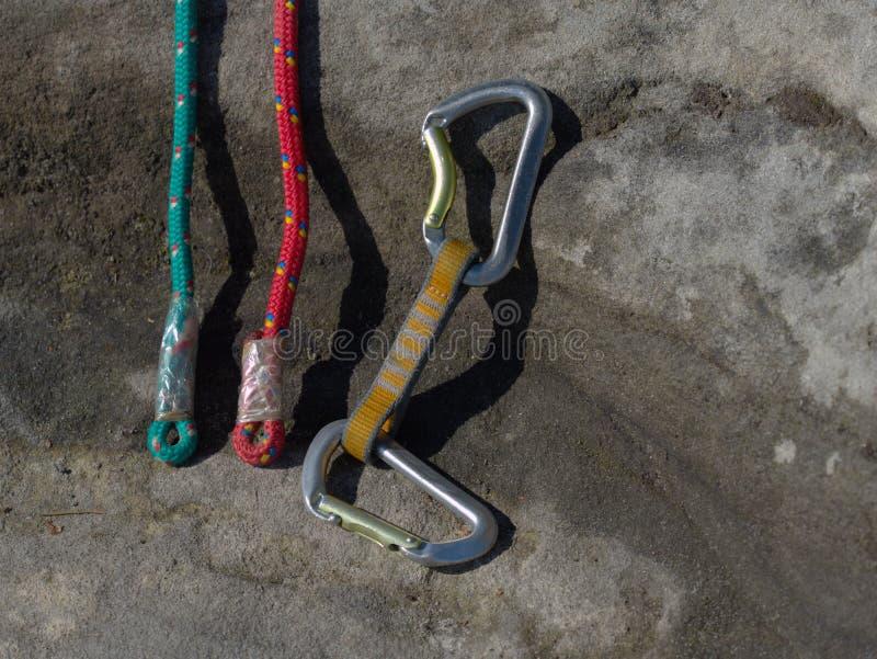Carabiners σφεντονών δεσμίδων στα χρησιμοποιημένα κόκκινα και πράσινα σχοινιά στοκ φωτογραφία