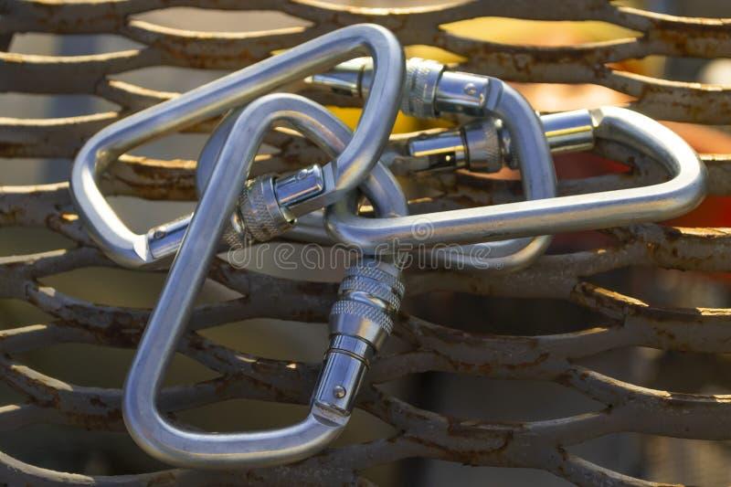 Carabiners de aço na malha expandida do metal Fundo industrial imagens de stock
