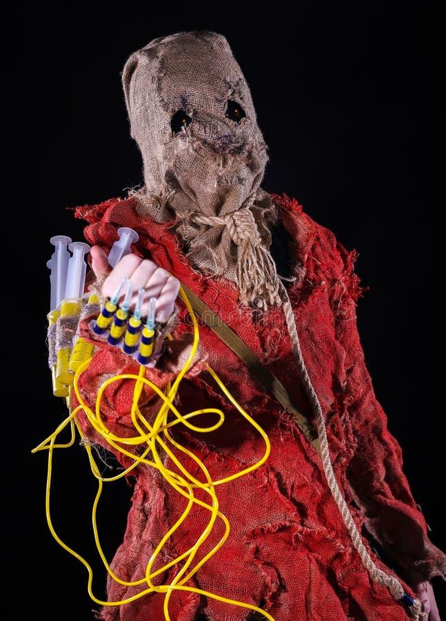 Caractère effrayant d'épouvantail dans un costume de toile à sac avec des seringues images libres de droits