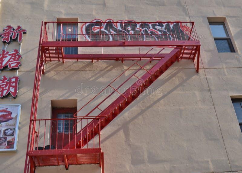 Caractères chinois de sortie de secours rouge de fond de NYC Chinatown sur le bâtiment photo libre de droits