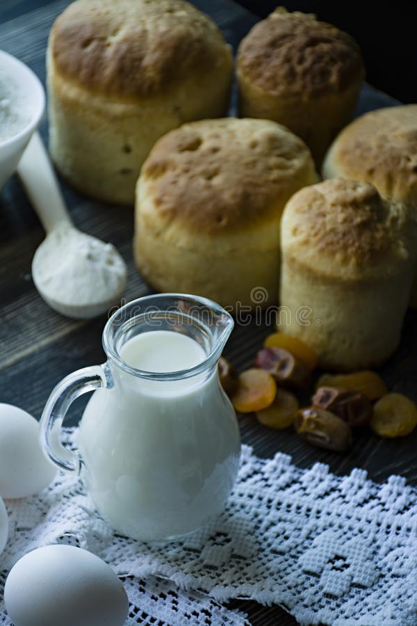 Carafe with milk in the background Easter cakes on a dark background. Fresh cakes with dried fruits. The process of cooking Easter stock images